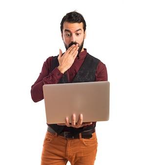 Zaskoczony mężczyzna ma na sobie waistcoat z laptopem