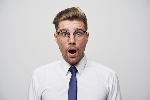 Zaskoczony mężczyzna, ma otwarte usta, oszołomiony, gdy coś reklamuje