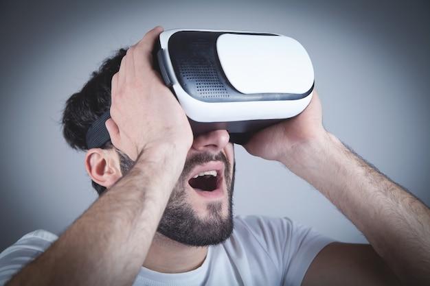 Zaskoczony mężczyzna nosi gogle wirtualnej rzeczywistości.