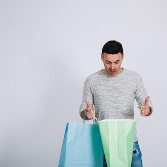 Zaskoczony mężczyzna patrząc w torbę na zakupy