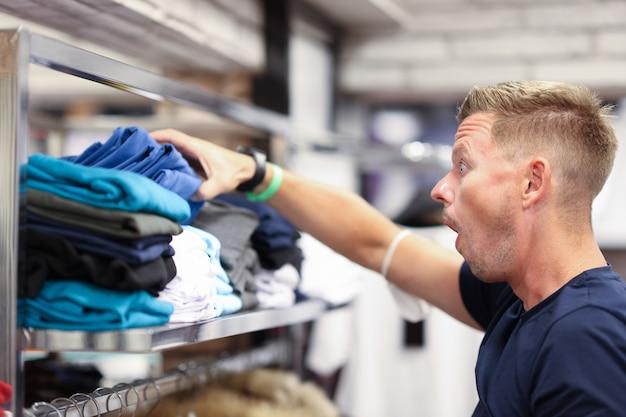 Zaskoczony mężczyzna patrzy na półkę z ubraniami w sklepach rabaty i wyprzedaże w centrach handlowych