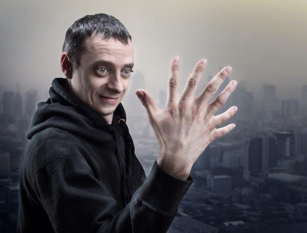 Zaskoczony mężczyzna patrzy na swoją dłoń siedmioma palcami