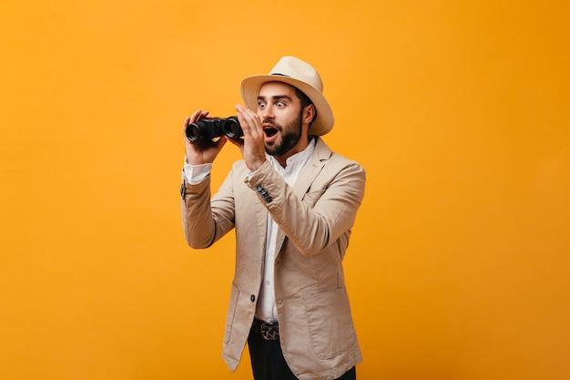 Zaskoczony mężczyzna patrzy w lornetkę na izolowanej ścianie