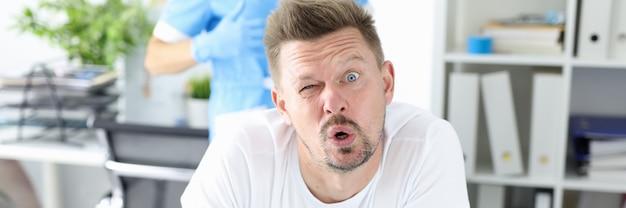 Zaskoczony mężczyzna przechodzi badanie lekarskie przez proktologa