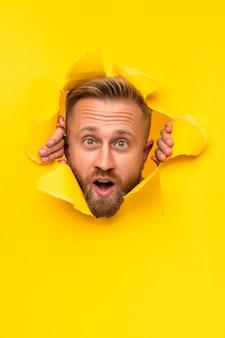Zaskoczony mężczyzna rozdziera żółty papier