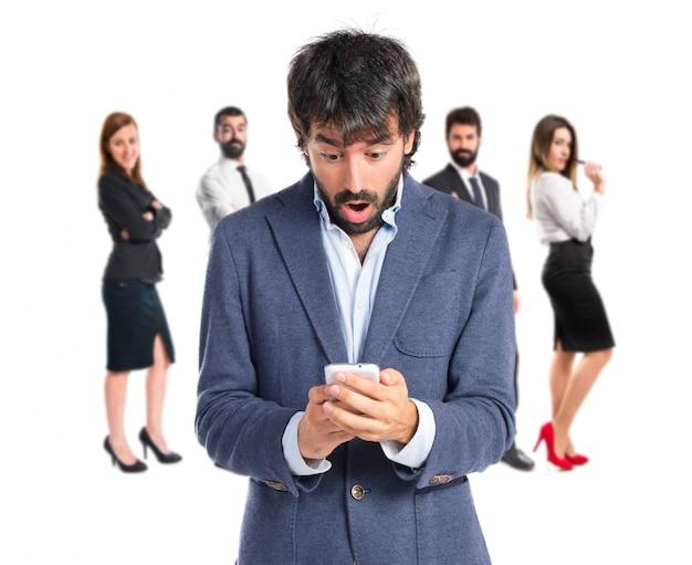 Zaskoczony mężczyzna rozmawia z telefonu komórkowego na białym tle
