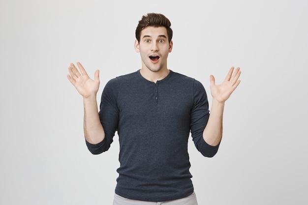 Zaskoczony mężczyzna sapiąc zdziwiony, unosząc ręce