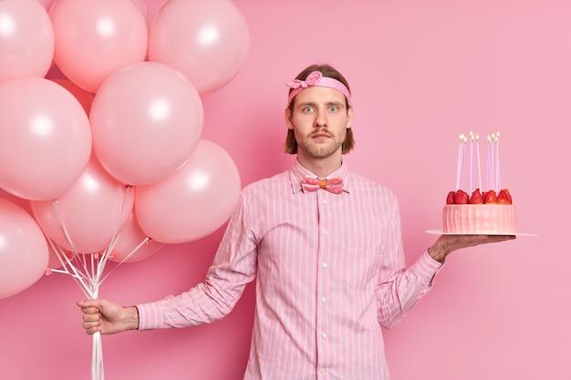 Zaskoczony mężczyzna świętuje urodziny trzyma bukiet balonów i tort truskawkowy ubrany w formalną muszkę w koszuli zszokowany widokiem wielu gości na imprezie odizolowanych na różowej ścianie