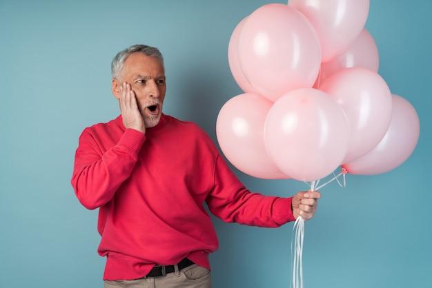 Zaskoczony mężczyzna trzyma różowe balony