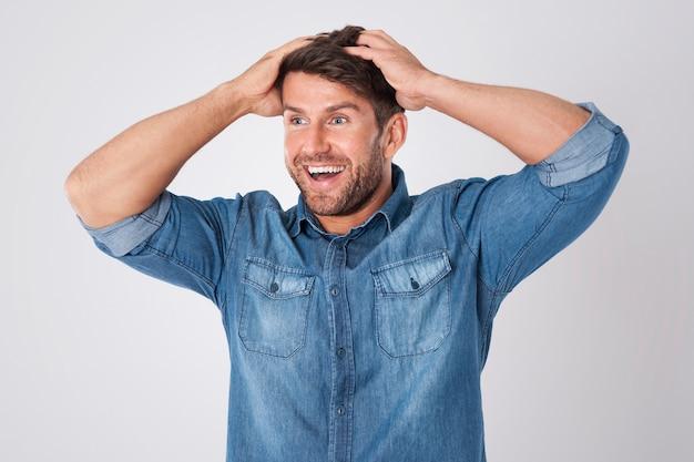 Zaskoczony mężczyzna w dżinsowej koszuli