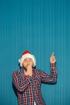 Zaskoczony mężczyzna w kapeluszu santa pokazujący cokolwiek na niebieskim tle