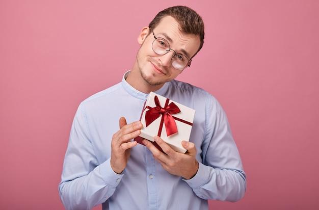 Zaskoczony mężczyzna w koszuli w okularach trzyma prezent w pudełku z pokrywką i czerwoną kokardą w dłoniach