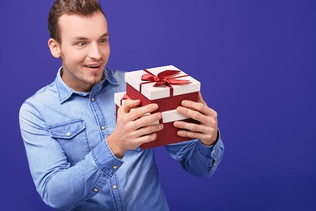 Zaskoczony mężczyzna w niebieskiej dżinsowej koszuli stojący z dwoma prezentami z czerwoną czapką