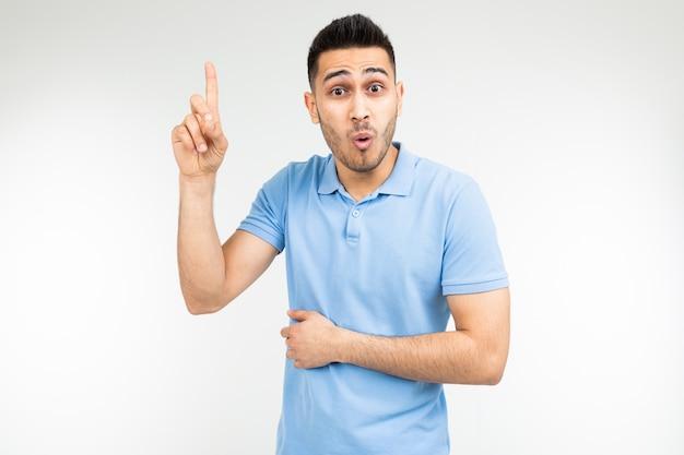 Zaskoczony mężczyzna w niebieskiej koszulce oferuje pomysł pokazujący kciuk do góry na białym