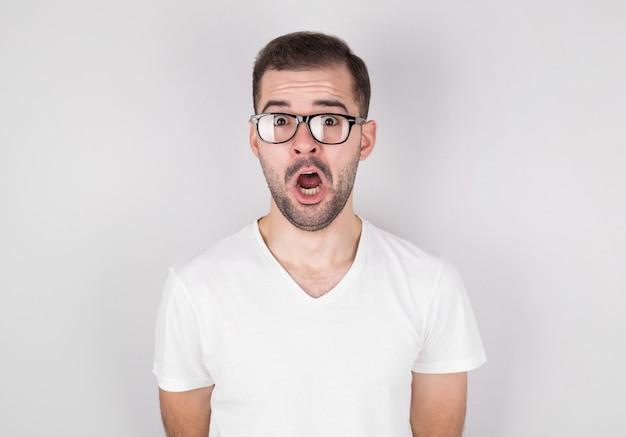 Zaskoczony mężczyzna w okularach na sobie biały podkoszulek na szarej ścianie