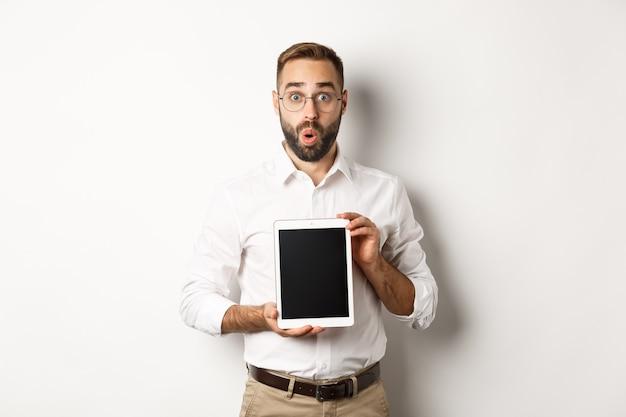 Zaskoczony mężczyzna w okularach, pokazujący ekran cyfrowego tabletu, wyglądający na zaskoczonego, stojący