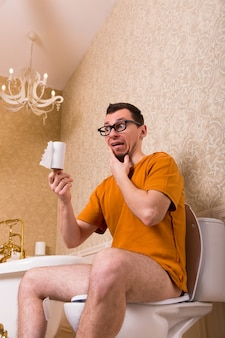 Zaskoczony mężczyzna w okularach siedzi na muszli klozetowej, z papieru