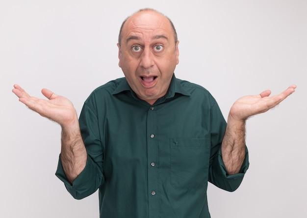 Zaskoczony mężczyzna w średnim wieku na sobie zieloną koszulkę, rozkładając ręce na białym tle na białej ścianie