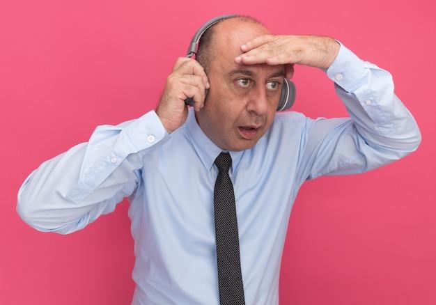 Zaskoczony mężczyzna w średnim wieku, ubrany w białą koszulkę z krawatem i słuchawkami, patrzący na odległość ręką odizolowaną na różowej ścianie