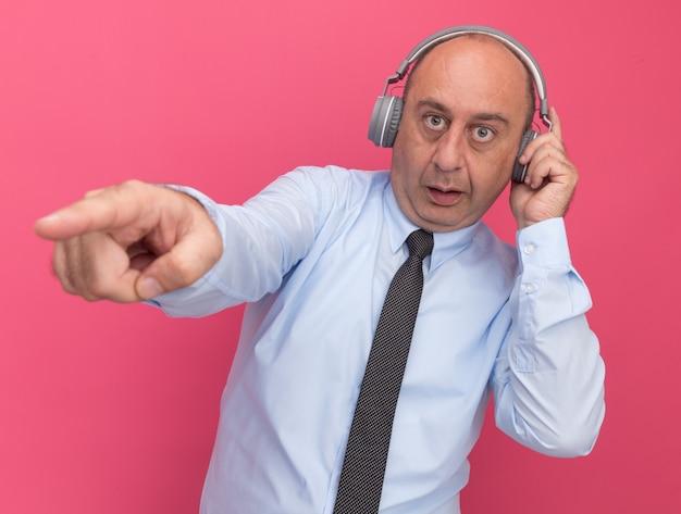 Zaskoczony mężczyzna w średnim wieku ubrany w białą koszulkę z krawatem i słuchawkami wskazuje na bok na białym tle na różowej ścianie