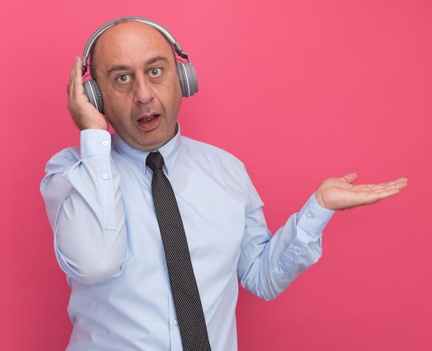 Zaskoczony mężczyzna w średnim wieku ubrany w białą koszulkę z krawatem i słuchawkami wskazuje ręką na boku odizolowaną na różowej ścianie z miejscem na kopię