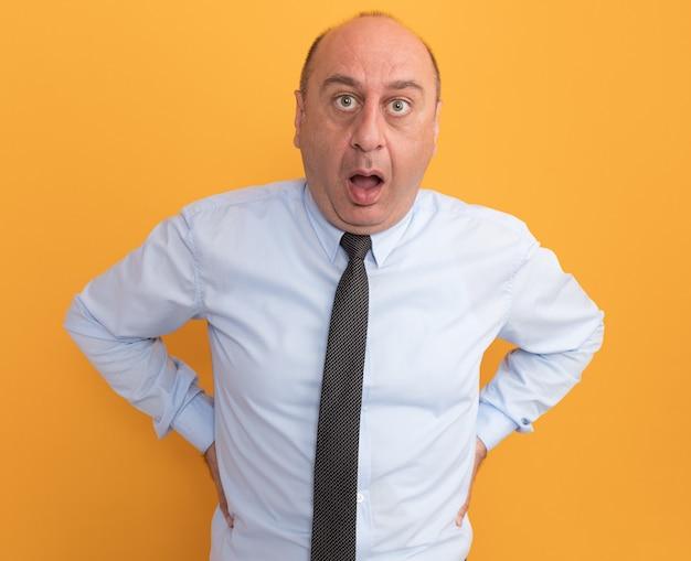 Zaskoczony mężczyzna w średnim wieku ubrany w białą koszulkę z krawatem, kładąc ręce na talii na białym tle na pomarańczowej ścianie