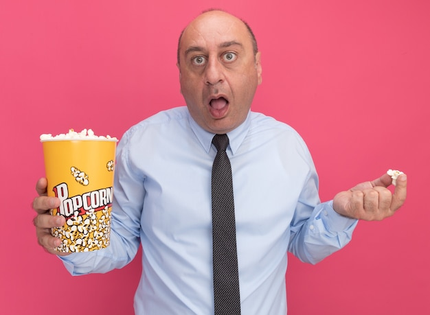 Zaskoczony mężczyzna w średnim wieku, ubrany w białą koszulkę z krawatem, trzymający wiadro popcornu i kawałek popcornu izolowane na różowej ścianie