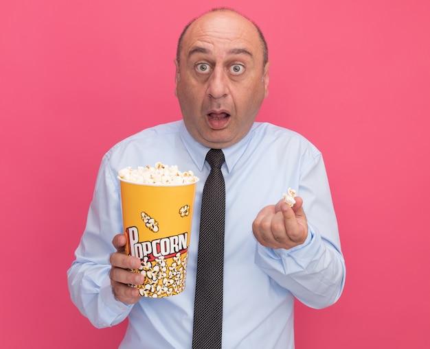 Zaskoczony mężczyzna w średnim wieku ubrany w białą koszulkę z krawatem trzymający wiadro popcornu z kawałkiem popcornu na różowej ścianie