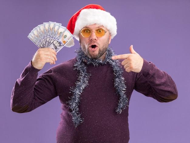 Zaskoczony mężczyzna w średnim wieku ubrany w czapkę mikołaja i świecącą girlandę na szyi w okularach trzymający i wskazujący pieniądze na fioletowej ścianie