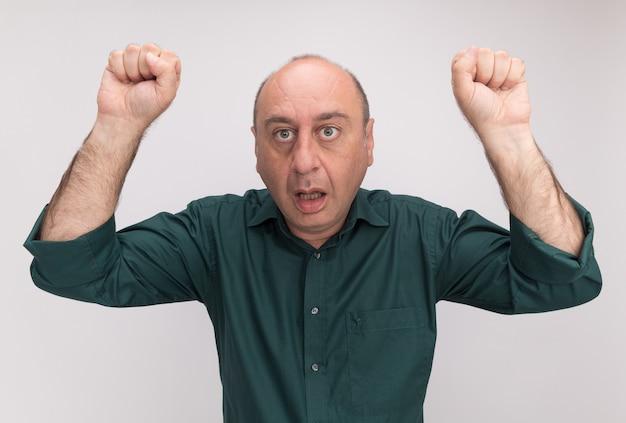Zaskoczony mężczyzna w średnim wieku, ubrany w zieloną koszulkę, podnoszący pięści na białym tle na białej ścianie