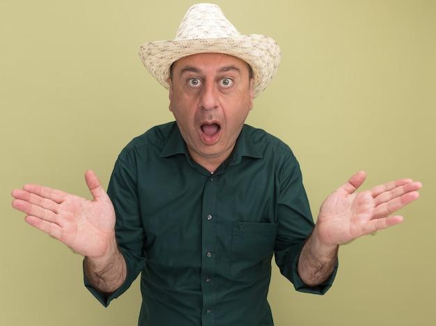 Zaskoczony mężczyzna w średnim wieku ubrany w zielony t-shirt i kapelusz, rozkładając ręce na białym tle na oliwkowej ścianie