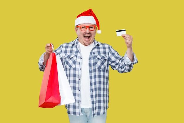 Zaskoczony mężczyzna w średnim wieku z otwartymi ustami w stylu casual i nowy rok czerwony kapelusz, stojąc, trzymając torby na zakupy i kartę kredytową ze zdziwioną twarzą, patrząc na aparat. studio strzał, odizolowane na żółtym tle