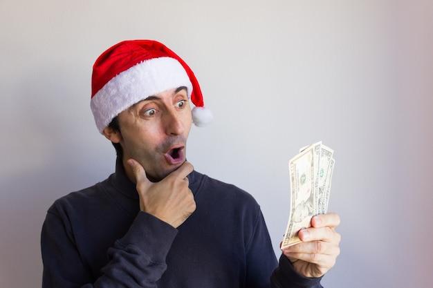 Zaskoczony mężczyzna w świątecznym kapeluszu trzymający banknoty dolarowe na białym tle nieoczekiwana premia pieniężna