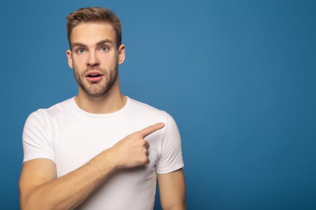 Zaskoczony mężczyzna wskazując palcem na bok na niebieskim tle