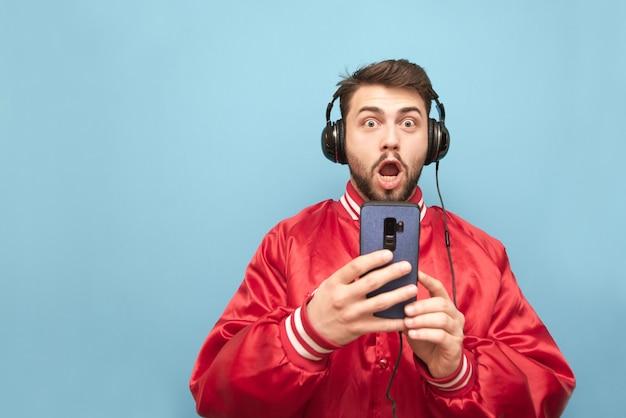 Zaskoczony mężczyzna z brodą w słuchawkach, trzyma w rękach smartfon