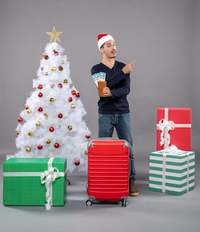 Zaskoczony mężczyzna z czerwoną walizką trzymający swoje bilety podróżne i wskazujący coś palcem na szaro