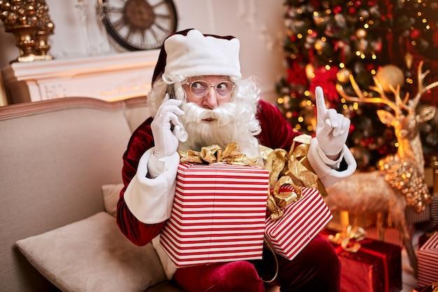 Zaskoczony mikołaj siedzi na kanapie i rozmawia przez telefon komórkowy przy kominku i choinki z prezentami. nowy rok i wesołych świąt, koncepcja wesołych świąt