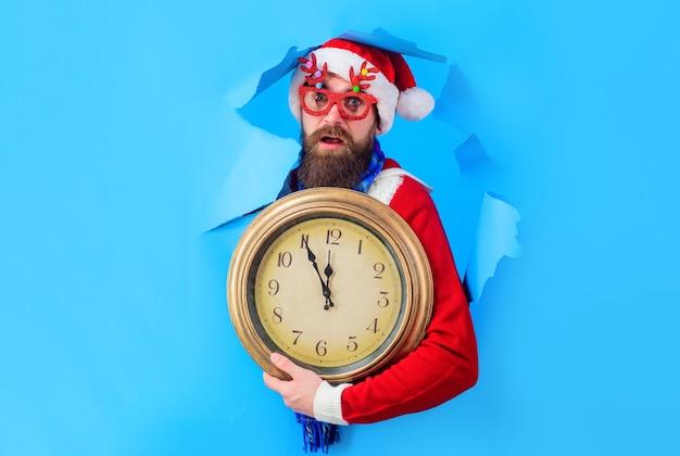 Zaskoczony mikołaj z zabytkowym zegarem przez papierową dziurkę odliczanie nowego roku czas świętować