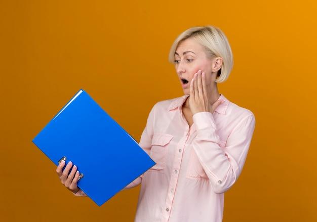 Zaskoczony młoda blond słowiańska kobieta trzymając i patrząc na folder kładąc dłoń na policzku na białym tle na pomarańczowej ścianie