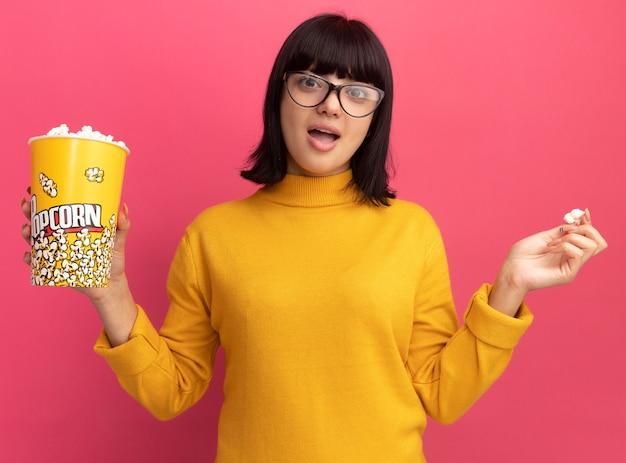 Zaskoczony, młoda brunetka kaukaska dziewczyna w okularach optycznych trzyma wiadro popcornu na różowo