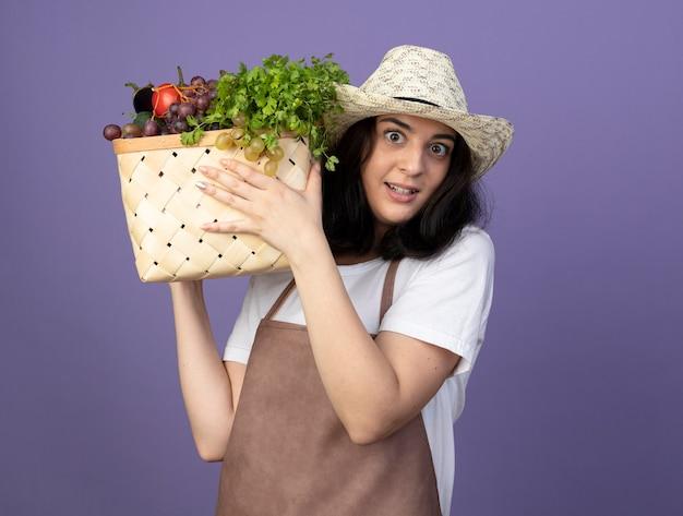 Zaskoczony, młoda brunetka ogrodnik kobieta w mundurze na sobie kapelusz ogrodniczy trzyma kosz warzyw na fioletowej ścianie z miejsca na kopię