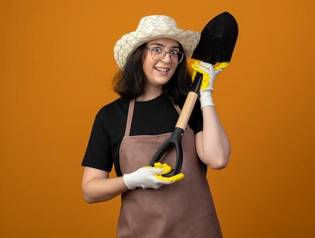 Zaskoczony, młoda brunetka ogrodnik żeński w okularach optycznych iw mundurze na sobie kapelusz ogrodniczy i rękawiczki trzyma łopatę na białym tle na pomarańczowej ścianie