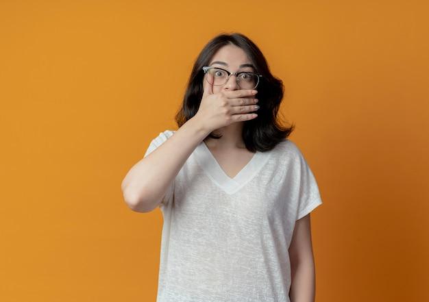 Zaskoczony, młoda dziewczyna dość kaukaski w okularach, kładąc rękę na ustach na białym tle na pomarańczowym tle z miejsca na kopię