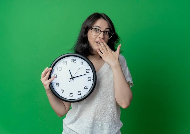 Zaskoczony, młoda dziewczyna dość kaukaski w okularach, trzymając zegar i kładąc rękę na ustach na białym tle na zielonym tle z miejsca na kopię