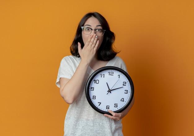 Zaskoczony, młoda dziewczyna dość kaukaski w okularach, trzymając zegar, kładąc rękę na ustach na białym tle na pomarańczowym tle z miejsca na kopię