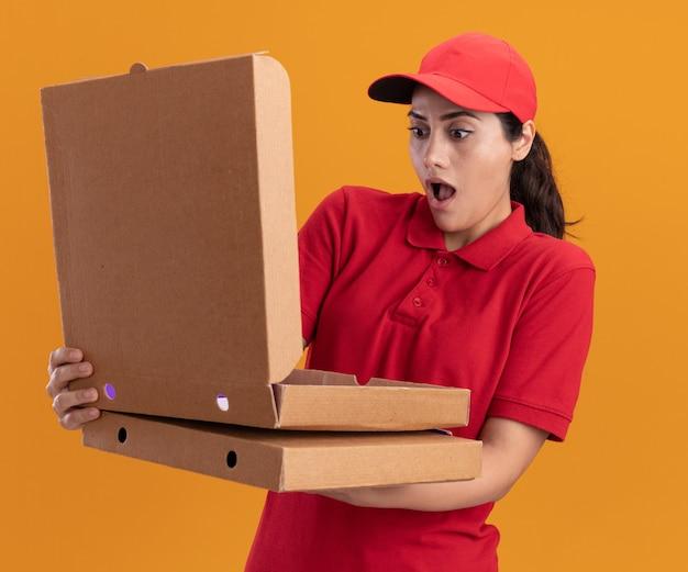Zaskoczony, młoda dziewczyna dostawy ubrana w mundur i czapkę, trzymając i otwierając pudełko po pizzy na białym tle na pomarańczowej ścianie