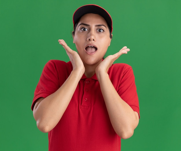 Zaskoczony, młoda dziewczyna dostawy ubrana w mundur i czapkę, trzymając się za ręce wokół twarzy na białym tle na zielonej ścianie