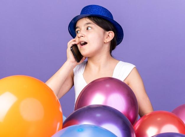 Zaskoczony młoda dziewczyna kaukaski ubrana w niebieski kapelusz strony rozmawia przez telefon patrząc na stronę stojącą z balonami helowymi na białym tle na fioletowej ścianie z miejsca na kopię