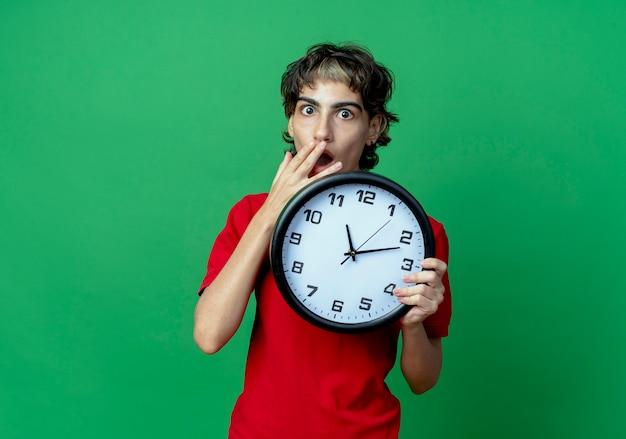 Zaskoczony, młoda dziewczyna kaukaski z fryzurą pixie, trzymając zegar z ręką na ustach na białym tle na zielonym tle z miejsca na kopię