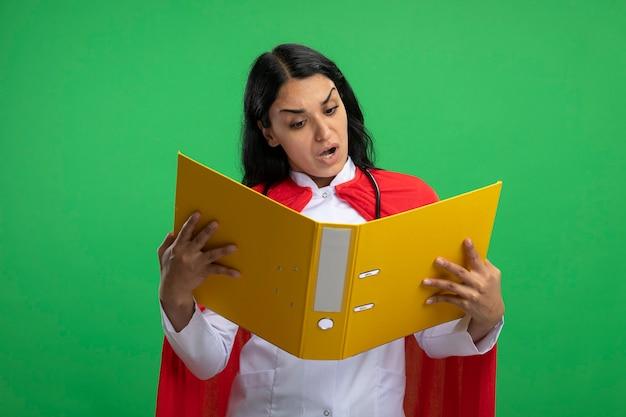 Zaskoczony, młoda dziewczyna superbohatera na sobie szlafrok medyczny ze stetoskopem, trzymając i patrząc na folder na białym tle na zielono
